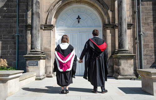 Graduating couple from the University of St Andrews holidng hands