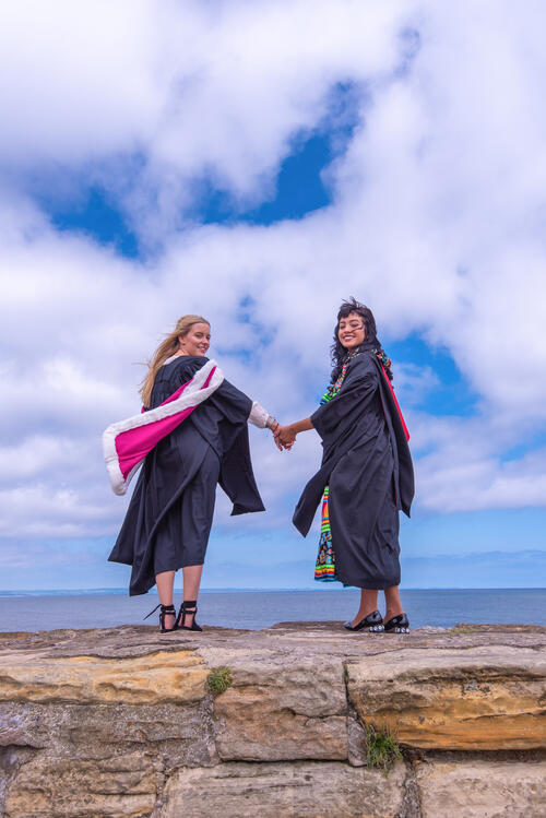 Two friends holding hands on St Andrews Pier following Graduating from the University of St Andrews