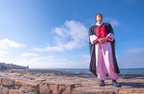 Graduate from the University of St Andrews in national dress on the Pier, St Andrews