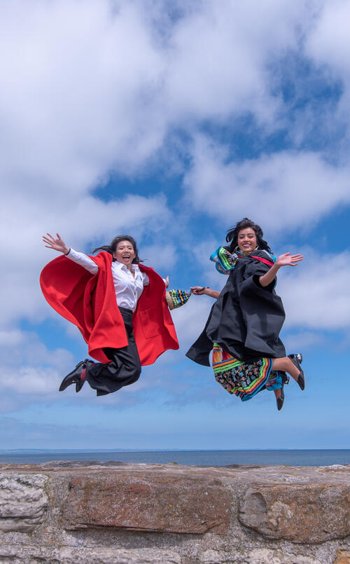Two friends from the University of St Andrews jumping on the Pier on Graduation Day