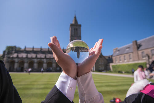 Hands holding lensball on Graduation Day at the University of St Andrews with St Salvator's Chapel tower