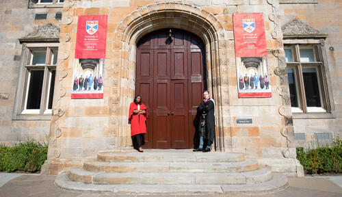 Fresh Graduate from the University of St Andrews in kilt with Undergraduate student in red gown