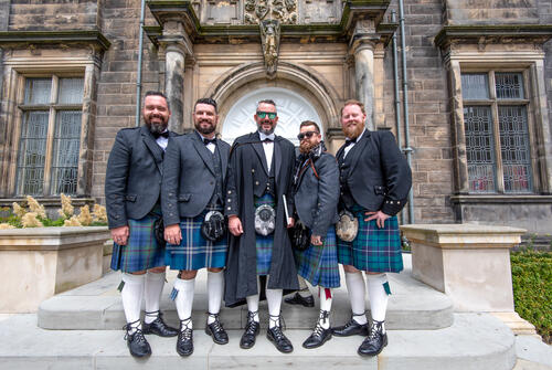 Graduate from Florida in traditional kilt dress with his family and friends at the University of St Andrews
