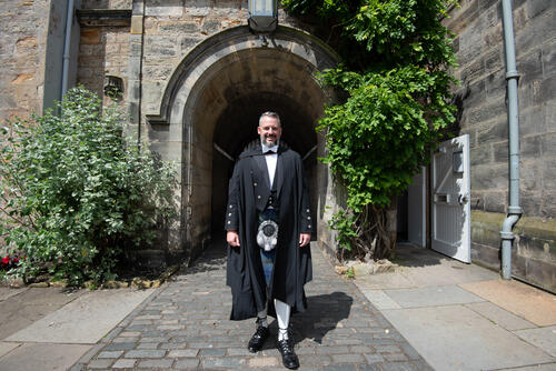 Graduate from Florida in traditional kilt dress at the University of St Andrews