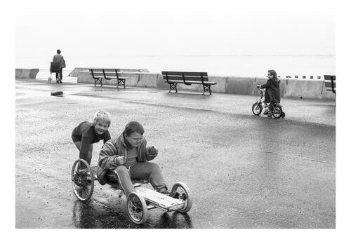 Young boys playing on a guider (made from pram wheels and wood), Portobello Promenade, Edinburgh.