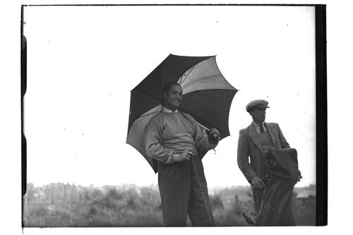 Golfer, under umbrella, and caddie, the Open Championship, St Andrews 1939.
