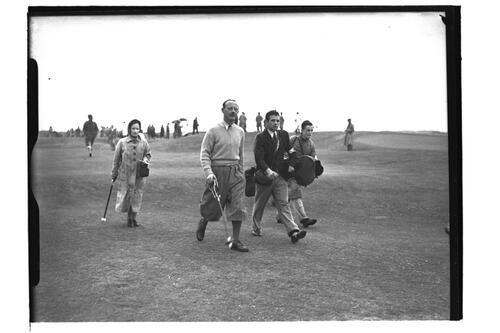 Golfer and caddies walk over the Old Course, the Open Championship, St Andrews 1939.