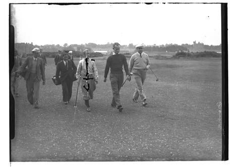 Golfers and caddies walk over the Old Course, the Open Championship, St Andrews 1939.