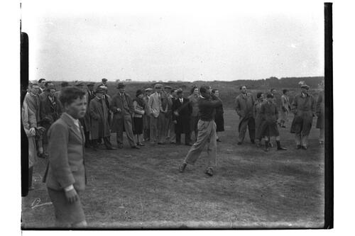 Golfer drives down the fairway, watched by crowd, at the British Amateur Championship, Troon.