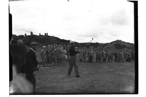 Golfer drives, watched by his caddie and the crowd, at the British Amateur Championship, Troon.