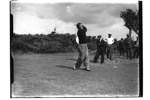Golfer tees off, watched caddies and golfers, at the British Amateur Championship, Troon.