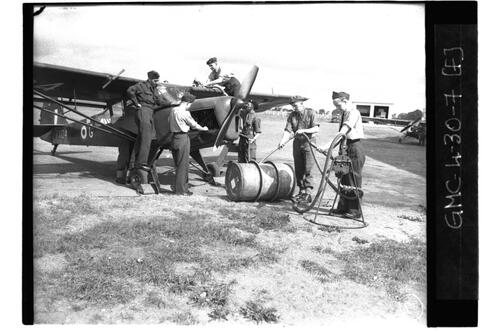 RAF ground crew re-fuelling and checking engine of plane, RAF Ouston.