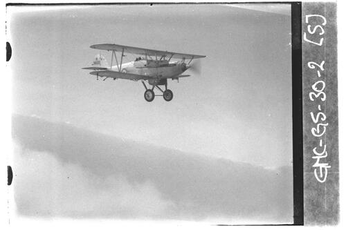 Biplane flying over the sea near Fife.