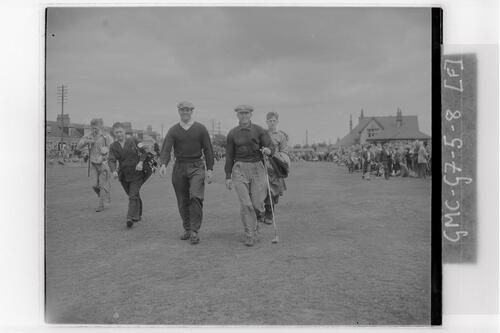 Two golfers and their caddies walk down the fairway at the Carnoustie Open Championship final rounds, 1953.