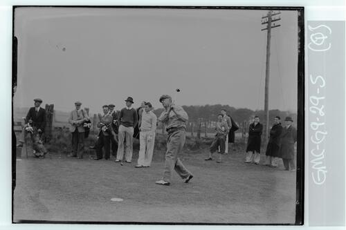 The Walker Cup Match 1934, Francis Ouimet tees off on the Old Course, St Andrews, watched by caddies and other golfers.
